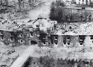 The battered Kholmsky Gate in June 1941 after its capture and its bullet-ridden facade below, today.