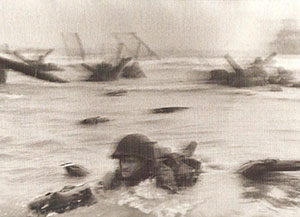 Robert Capa took this iconic photograph of an American soldier struggling in the surf under fire from German strongpoint WN 62 shown below, on the high ground today.